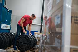 A worker moving rolls of metal in inventory warehouse.
